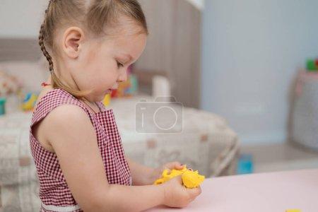 Photo pour Petite fille avec un beau jeu de visage avec des formes de moulage en argile, apprendre en jouant avec de la plasticine colorée développer la créativité - image libre de droit