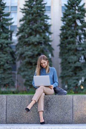 Photo pour Jeune femme blonde utilisant la technologie en plein air - image libre de droit