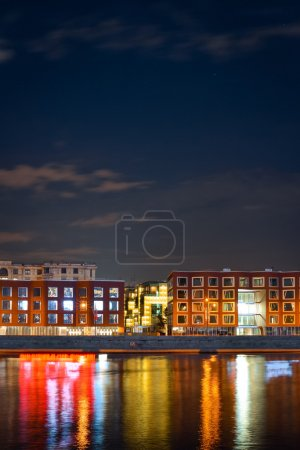 Night view from another side of the river from embankment to business buildings and reflection on water from window light