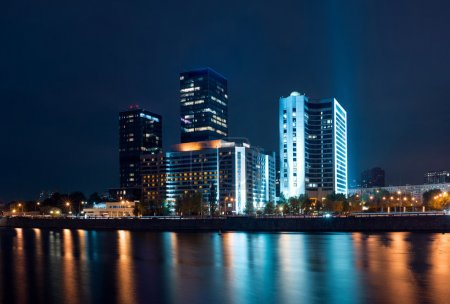 Night view on Moscow World Trade Center from bridge with reflections on water