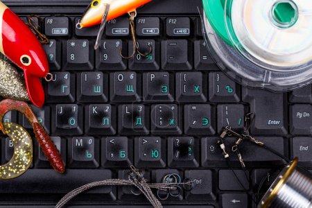 fishing tackles, line, lure, swimbait on keyboard