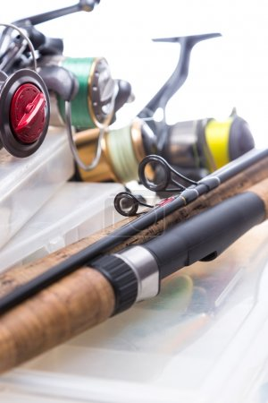 fishing reels and rods on storage boxes