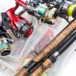 Different fishing reels and rods on storage boxes ...
