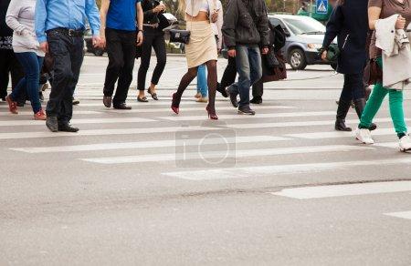 legs of pedestrians on a pedestrian crossing