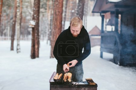man a fish fry on the grill in the winter forest