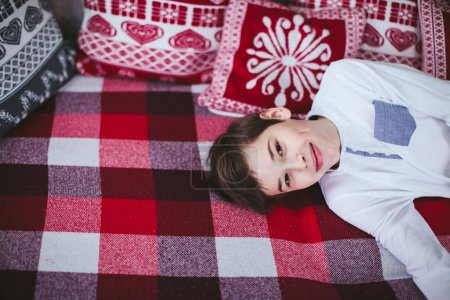 Teen lying on the couch with a plaid and pillows