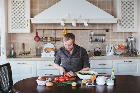 bearded man preparing vegetable salad in the kitchen