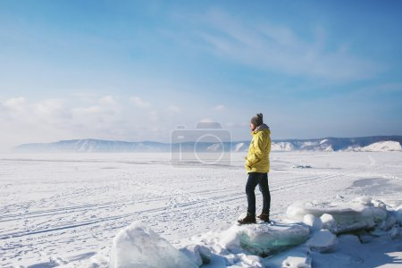 a man standing on the ice fault on a frozen Lake