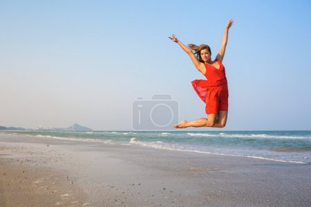 Sexy girl in red dress jumping