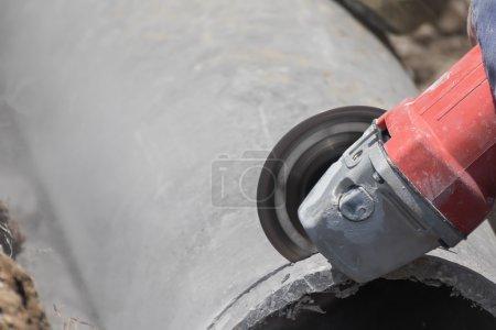 Plumbers cutting concrete water pipes