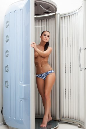 Sexy topless brunette posing in tanning booths
