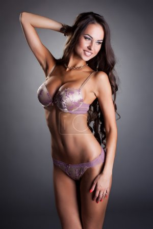 Attractive tanned woman in erotic pink lingerie