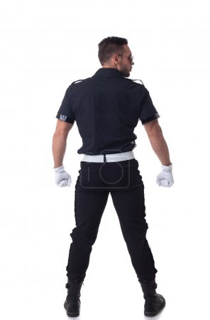 Fashionable muscular cop posing back to camera