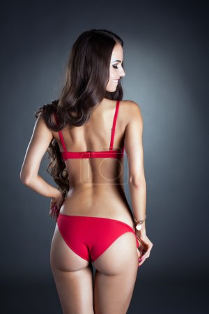 Rear view of flirting brunette in red lingerie