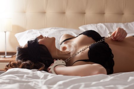 Image of pretty young submissive lying in bed