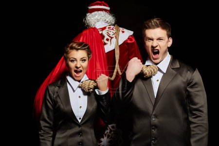 Photo for Financial concept of Christmas expenses. Screaming businessmen tied to Santa Claus - Royalty Free Image