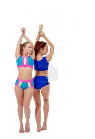 Beautiful girls practicing fitness in paired