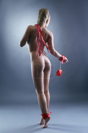 Rear view of naked blonde posing with sex toys