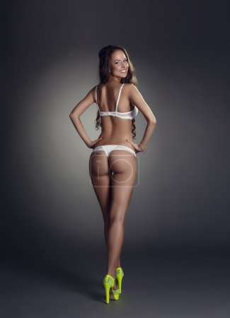 Rear view of smiling tanned model in underwear