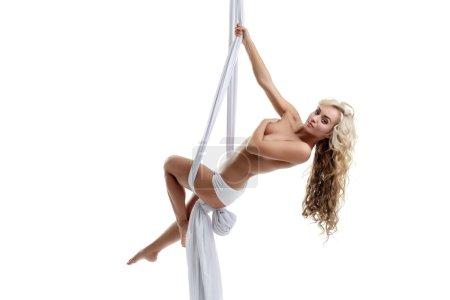 Flirtatious blonde posing topless on aerial swing