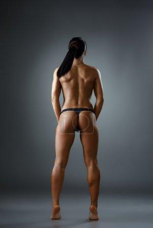 Rear view of female bodybuilder posing topless