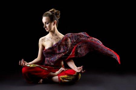 Beautiful calm woman meditates in lotus position