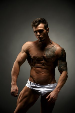 Bodybuilder advertises underwear. Studio photo