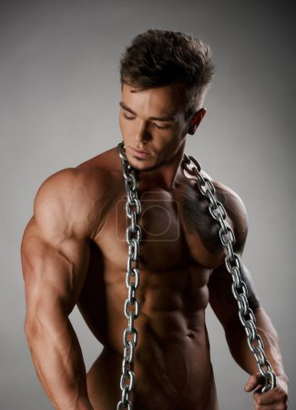 Strong athlete with perfect body posing naked