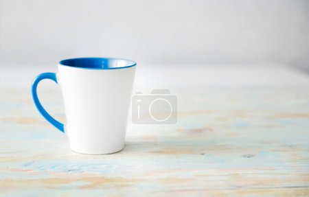Photo for White cup with blue handle and inner surface close up - Royalty Free Image