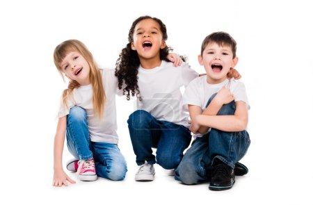 Photo pour Trois drôles d'enfants branchés rient assis sur le sol isolé sur fond blanc - image libre de droit
