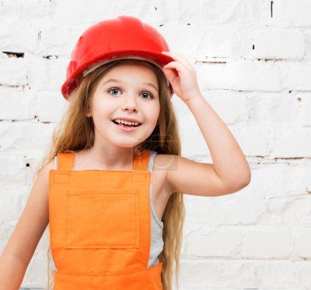Photo pour Petite fille souriante en uniforme de réparateur rouge et orange - image libre de droit
