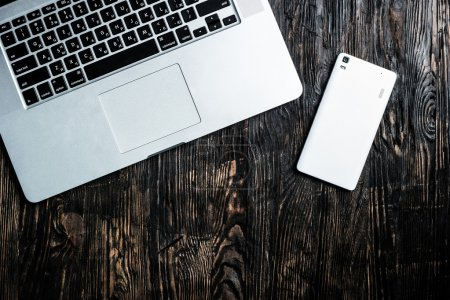 Grey open notebook and white smartphone on table