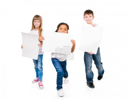 Three funny children holding paper blanks in hands