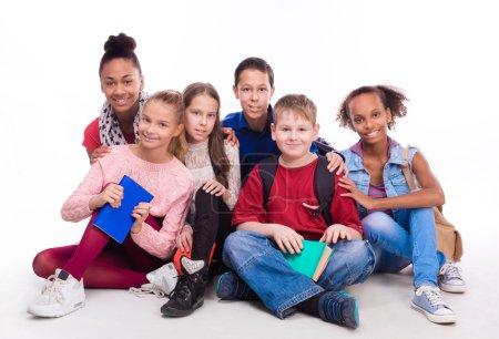 Group of schoolmates sitting on the floor