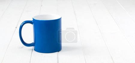 Photo for Blue cup with white inside on white wooden table - Royalty Free Image