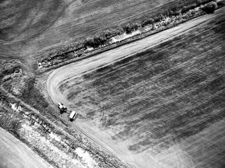 Photo for View from above on harvester plowing field, black and white photo - Royalty Free Image