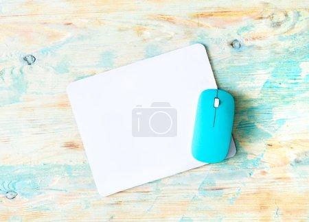 Photo pour Coussin blanc avec souris bleue sur fond en bois coloré - image libre de droit