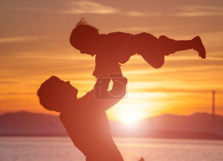 Photo pour Silhouette de mère qui retourne son enfant contre un coucher de soleil - image libre de droit