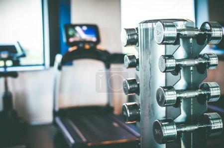 Photo pour Stand avec un haltère dans la salle de gym - image libre de droit