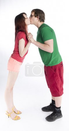 Couple Kissing While Standing and Holding Hands