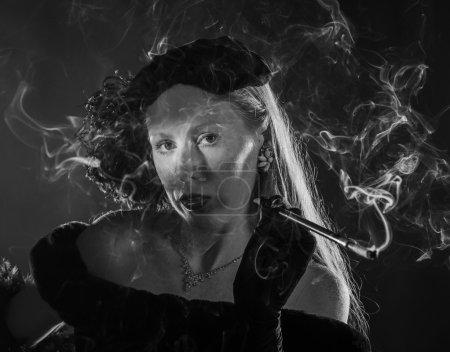 Photo pour Portrait noir et blanc de femme glamour fumant de la cigarette et vêtu de vêtements vintage, tête et épaules Portrait dans les années 1940 Film Noir Style - image libre de droit