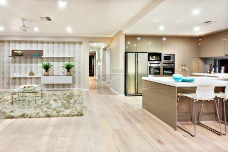 Photo pour La vue de l'image décrit à quoi ressemble la cuisine et le salon dans une maison de luxe et les deux peuvent voir au même endroit. Il y a un tapis de laine sur le sol avec des tables et des canapés dans le salon, il y a aussi un comptoir blanc avec des chaises et - image libre de droit