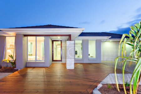 Front of the lights turned on modern mansion with wooden floor a