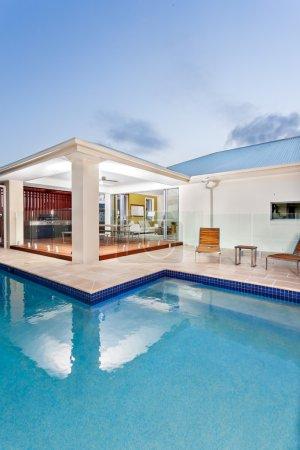 Photo pour Vue proche d'une piscine moderne avec une lumière de couleur sombre se propage à l'eau dans la soirée ou à l'aube. Sky a une zone de lumière dans le coin sur le toit de la maison et surtout sombre avec petits nuages qui donne un look sympa. La chambre en face de la piscine - image libre de droit