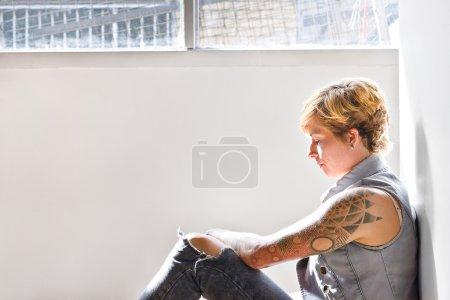 Photo pour Jolies filles avec des tatouages et une couleur d'or plus courts cheveux essayer de se concentrer sur un problème s'appuie sur le mur et assis sur le sol dans une pièce à côté d'une fenêtre - image libre de droit