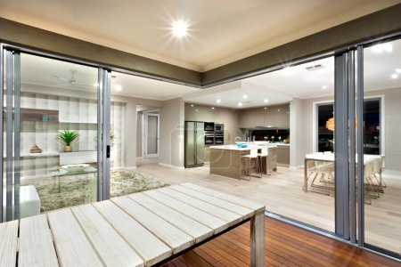 inside view of a modern house lights turned on with wooden table