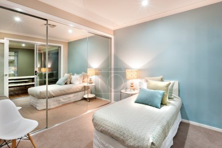 Small bedroom with pillows on the a single bed and lights turned
