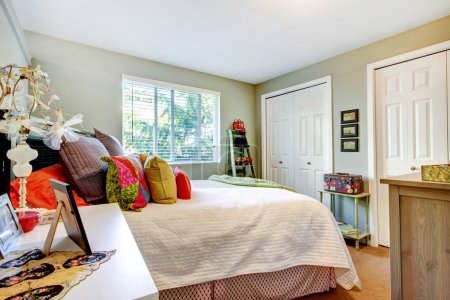 Photo for Guest bedroom with dual closets, white bedding, and colorful pillows. - Royalty Free Image