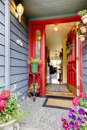 Bright red open front door to blue house with hardwood floor int