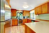 Kuchyně s světle hnědé skříňky a dřevěné desky